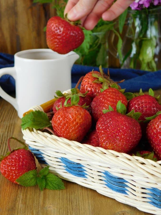 Erdbeeren in einem Weidenkorb und in einer Soße in einem keramischen Krug lizenzfreie stockbilder