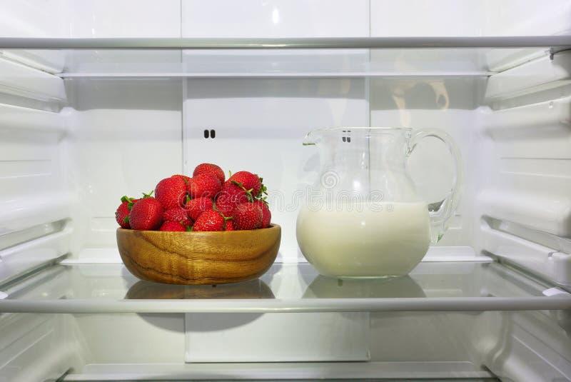 Erdbeeren in einer hölzernen Schüssel und in einem Pitcher Milch auf einem Regal im Kühlschrank stockbilder