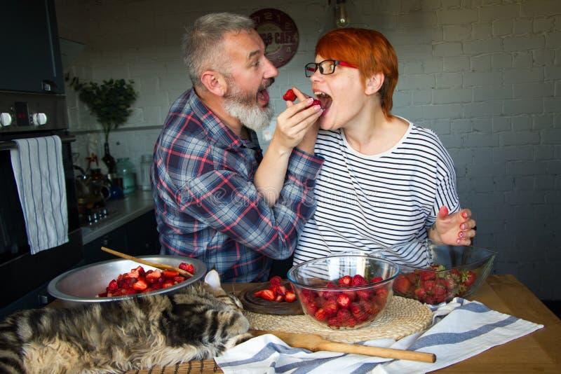 Erdbeeren erwachsener Paarmann und der Frauenschale und -schnittes für Erdbeermarmelade, ziehen sich, Spaß, Maine Coon zu lachen  stockfoto