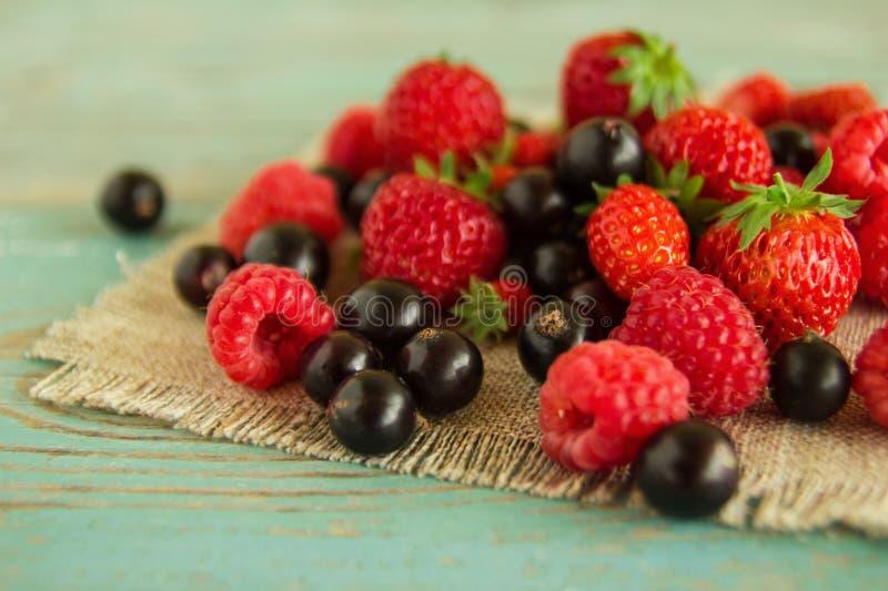 Erdbeeren, Himbeeren und schwarze Johannisbeeren auf den Servietten vom Sackleinen auf dem blau-weißen hölzernen Hintergrund lizenzfreie stockfotografie