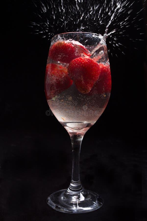 Erdbeeren im Weinglas mit Wasser stockfotografie