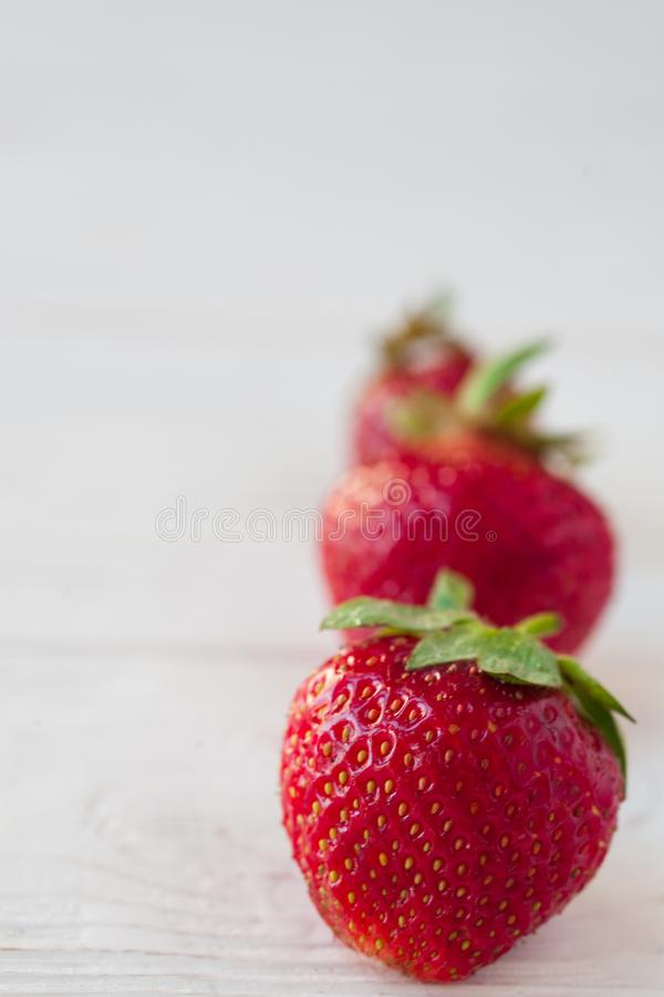Erdbeeren reif auf einem weißen hölzernen Hintergrund stockfotos