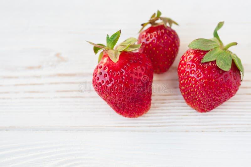 Erdbeeren reif auf einem weißen hölzernen Hintergrund stockfotografie