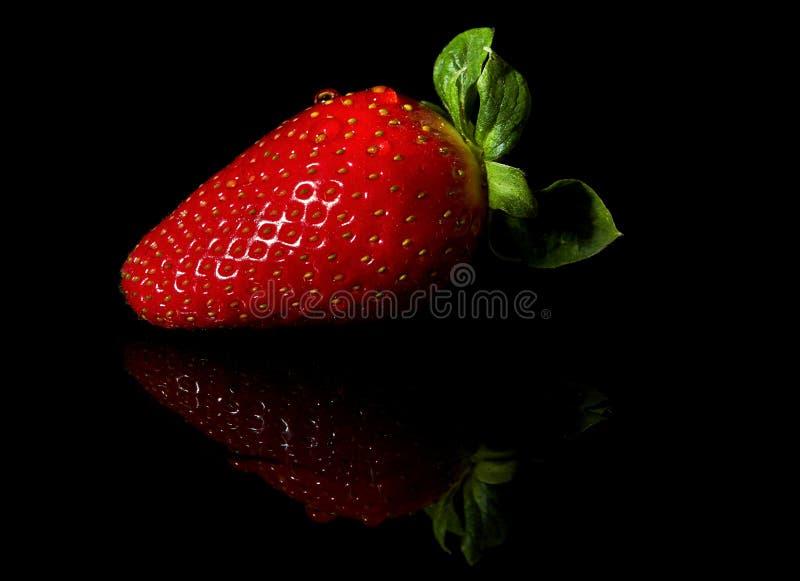 Erdbeeren saftig und reif auf einem schwarzen Hintergrund stockfotografie