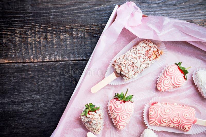 Erdbeeren und Bananen bedeckt mit Schokolade auf dem rustikalen Hintergrund lizenzfreies stockbild
