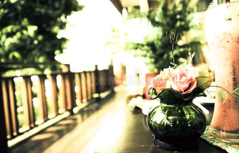 Erdbeeresmoothiecafé auf dem Terrassenrandfokus Vasen-Weinlesehintergrund stockfotos