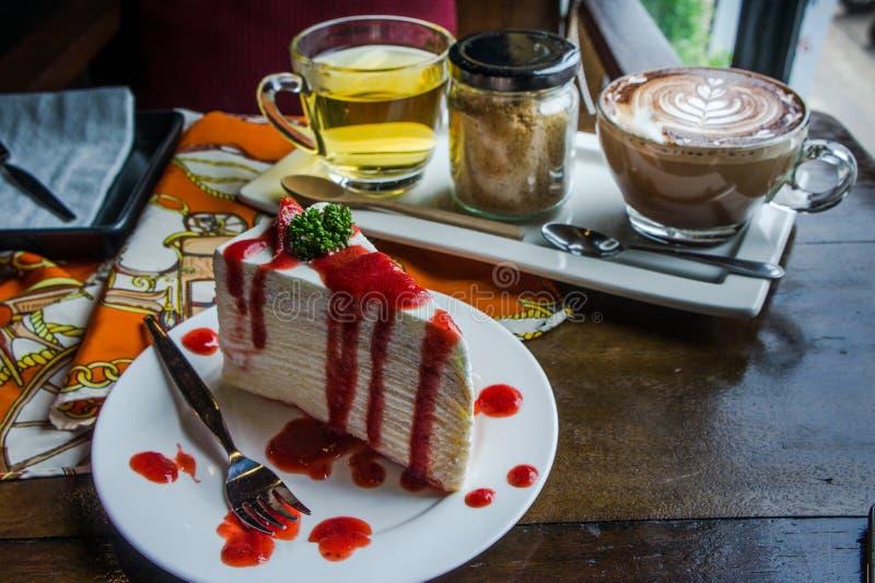 Erdbeerkreppkuchen auf hölzerner Tabelle in der Kaffeestube, Nachtisch tas stockfotografie