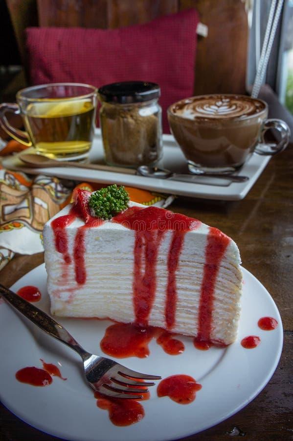 Erdbeerkreppkuchen auf hölzerner Tabelle in der Kaffeestube, Nachtisch tas lizenzfreies stockfoto
