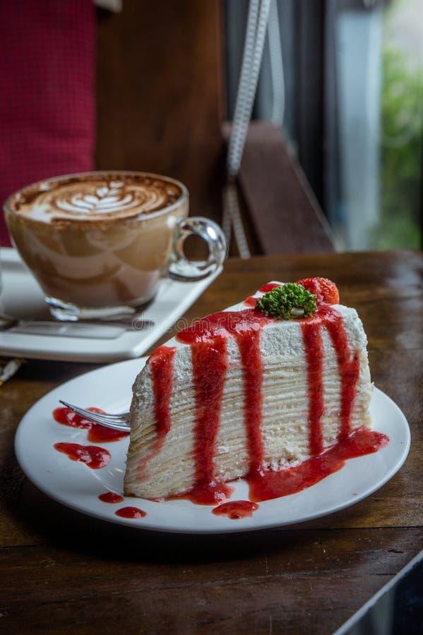 Erdbeerkreppkuchen auf hölzerner Tabelle in der Kaffeestube, Nachtisch tas lizenzfreie stockbilder