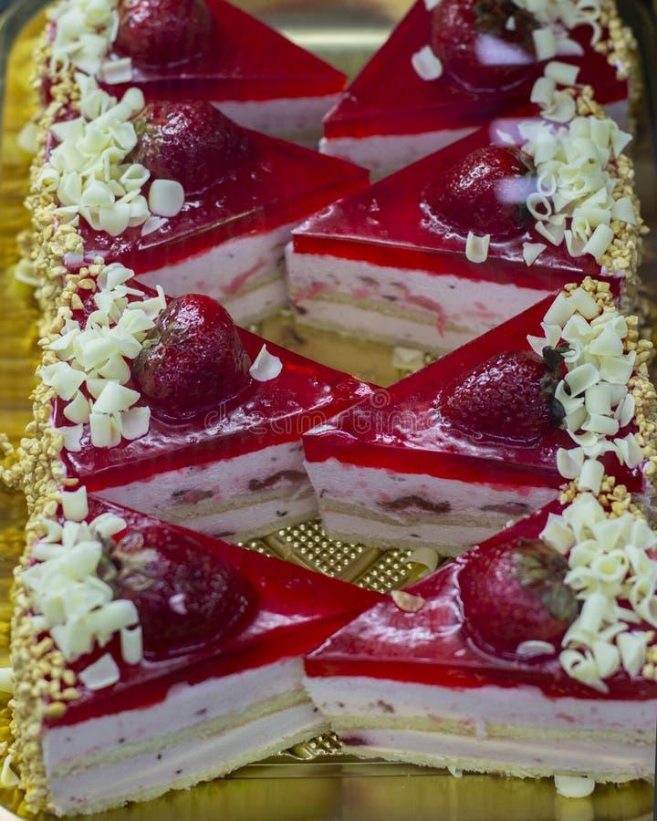 Erdbeerkuchen mit Schichten Auflauf und Keks, Erdbeermarmelade mit Beeren und Schokoladensplittern, besprüht mit gehackten Nüssen lizenzfreie stockfotografie