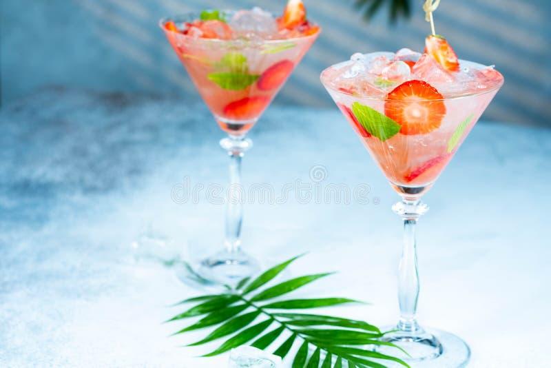 Erdbeerlimonade oder Alkoholikercocktail mit Eissirupsoda und tadellose Bl?tter auf Bartisch stockfotografie