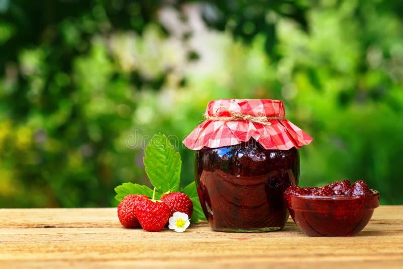 Erdbeermarmelade auf Holztisch lizenzfreie stockfotografie