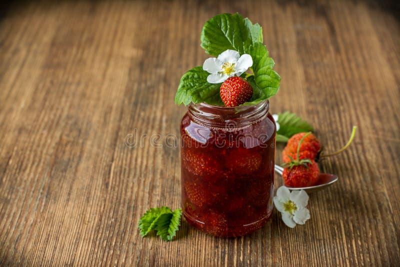 Erdbeermarmelade in einem Glasgefäß mit Erdbeeren an lizenzfreie stockfotografie