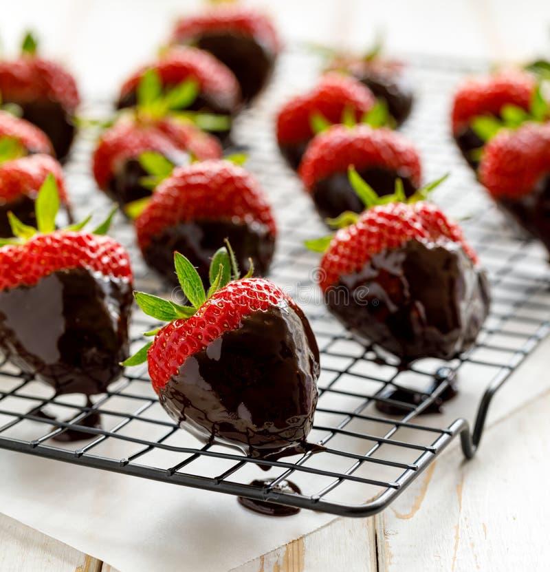 Erdbeernachtisch, dunkle Schokolade bedeckte Erdbeeren, frische Erdbeeren eintauchte in geschmolzene dunkle Schokolade lizenzfreies stockbild