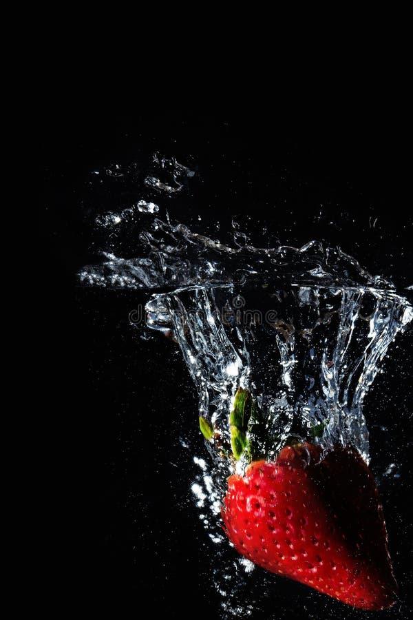 Erdbeerspritzen im Schwarzen lizenzfreie stockbilder