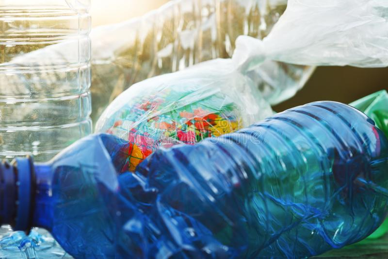 Erdkugel oben eingewickelt in der transparenten Plastiktasche und in den leeren benutzten Plastikwasserflaschen Hintergrund, Absc lizenzfreie stockfotos