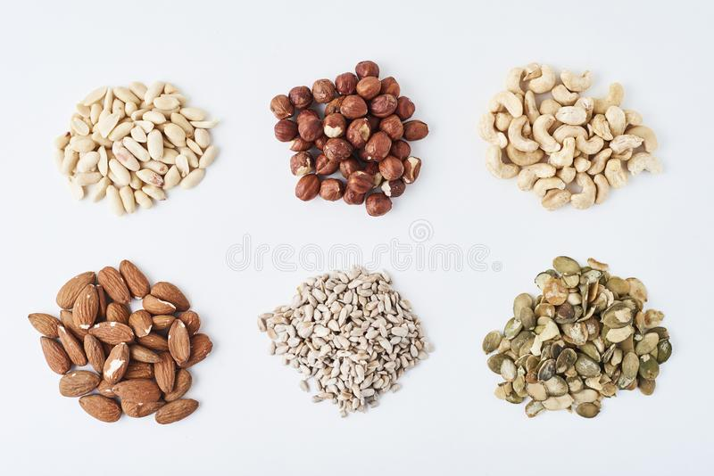 Erdnüsse, Acajoubäume, Haselnüsse, Mandeln, Kürbiskerne und Sonnenblumensamen auf einem weißen lokalisierten Hintergrund lizenzfreie stockbilder