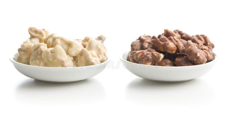 Erdnüsse bedeckten weiße und dunkle Schokolade stockfotos