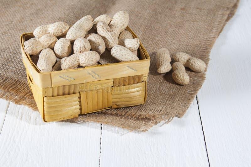 Erdnüsse in einem Weidenkorb, nahe drei Erdnüssen auf Sackleinen Weißer hölzerner Hintergrund Gesunde Nahrung und Gesundheitswese lizenzfreie stockbilder