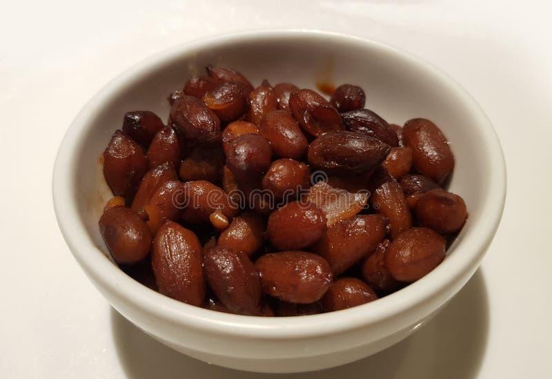 Erdnüsse getränkt in der Sojasoße in der weißen Schüssel auf weißer Platte lizenzfreies stockfoto