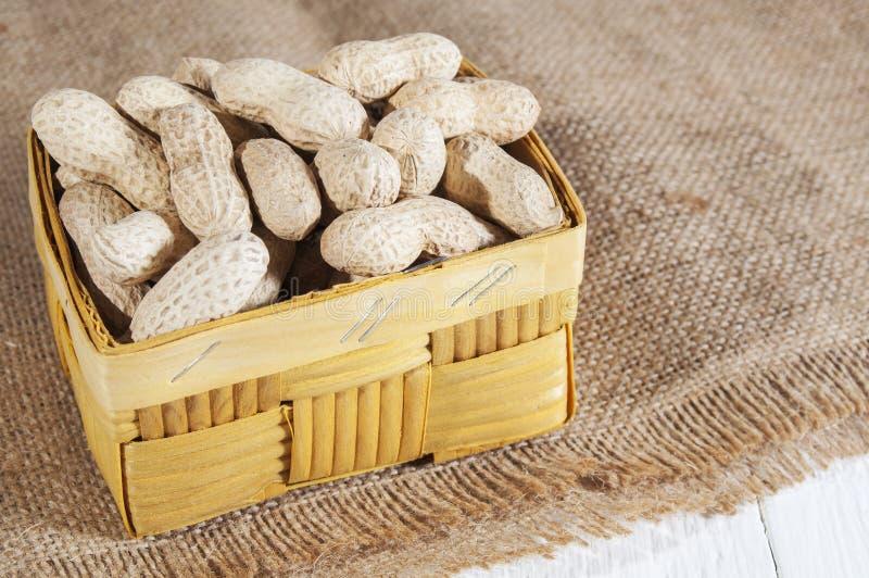 Erdnüsse im Korb auf einer Leinwand auf einem weißen Holztisch Gesunde Nahrung für die Leute beschäftigt gewesen mit dem Sport un lizenzfreie stockfotos