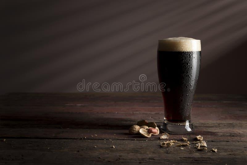 Erdnüsse und dunkles Bier stockfotos