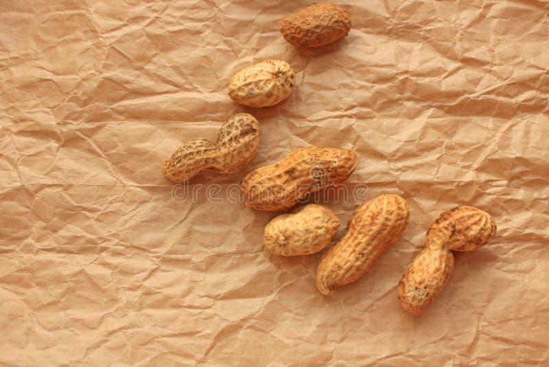 Erdnuss in einem Oberteil auf Kraftpapier, Nahrungsmittelhintergrund von Erdnüssen lizenzfreie stockfotografie