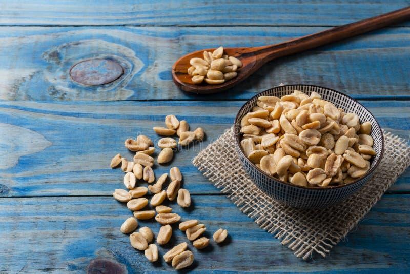 Erdnuss innerhalb des keramischen Topfes über blauem Kiefernholz stockbilder