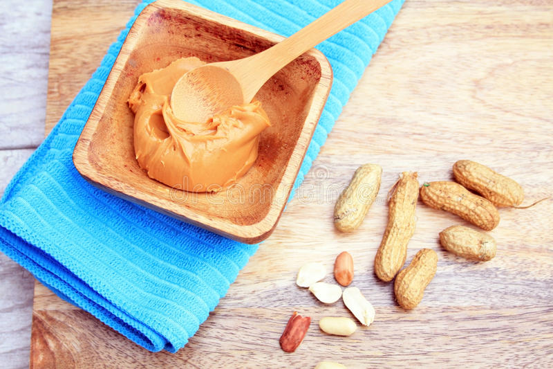 Erdnussbutter in einer hölzernen Schüssel mit hölzernem Löffel mit Erdnüsse cra stockfotos