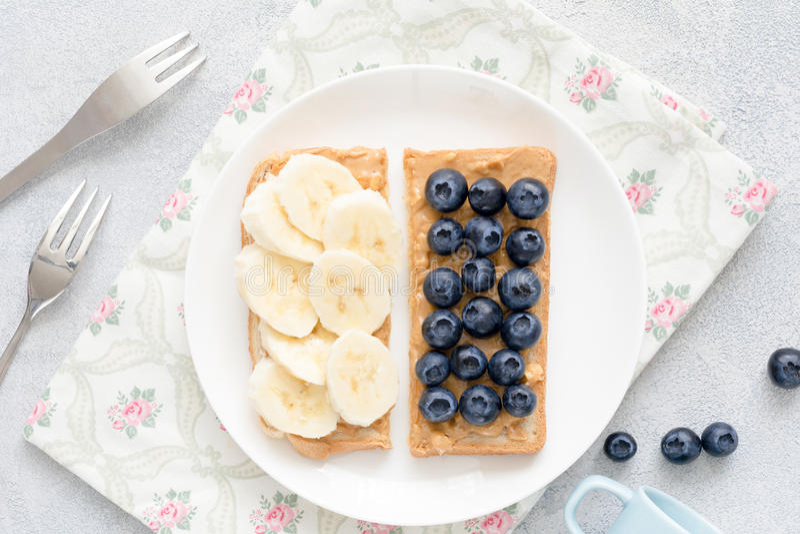 Erdnussbuttertoast mit Banane und Blaubeeren stockfoto