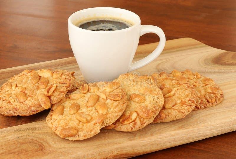 Erdnussgruppenkekse und schwarzer Kaffee in einer weißen Schale lizenzfreie stockfotos
