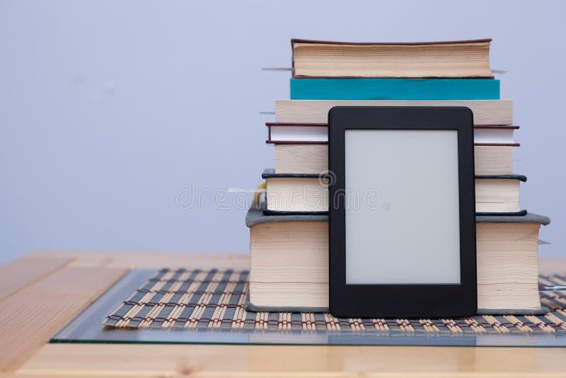 EReader in bianco davanti ad una torre dei libri con i segnalibri fotografie stock