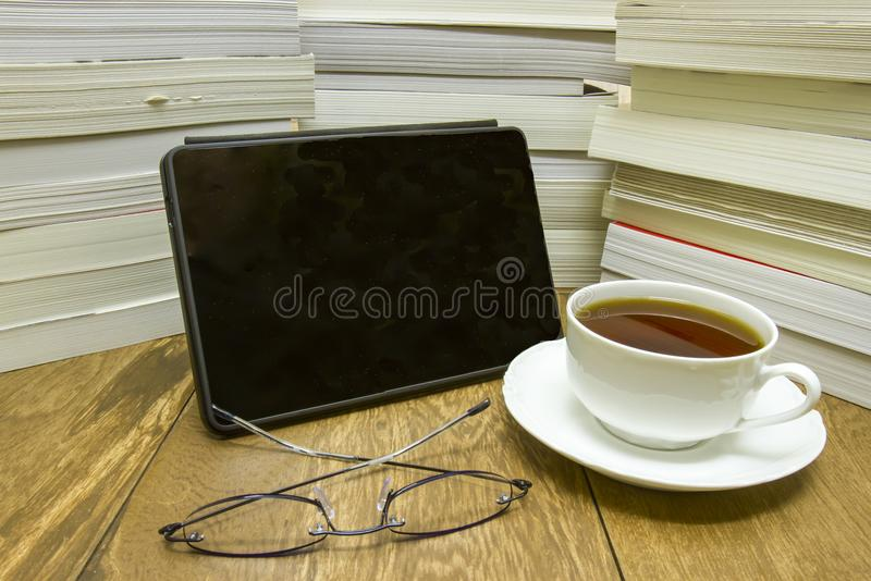 EReader with books, reading glasses and cup of tea. EReader next to pile of paperback and hardback novels on wood with reading glasses and cup of tea royalty free stock photos