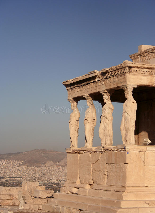 Erechtheion at Acropolis in Athens. Porch and female statue columns of the Erechteion at Acropolis with city and sky to the left and back royalty free stock photography