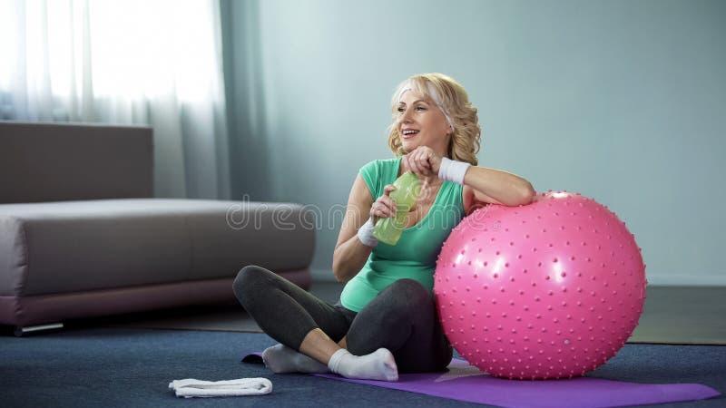 Erfüllte ältere Frau mit der Flasche Wasser entspannend nach Training, Sport stockfotos