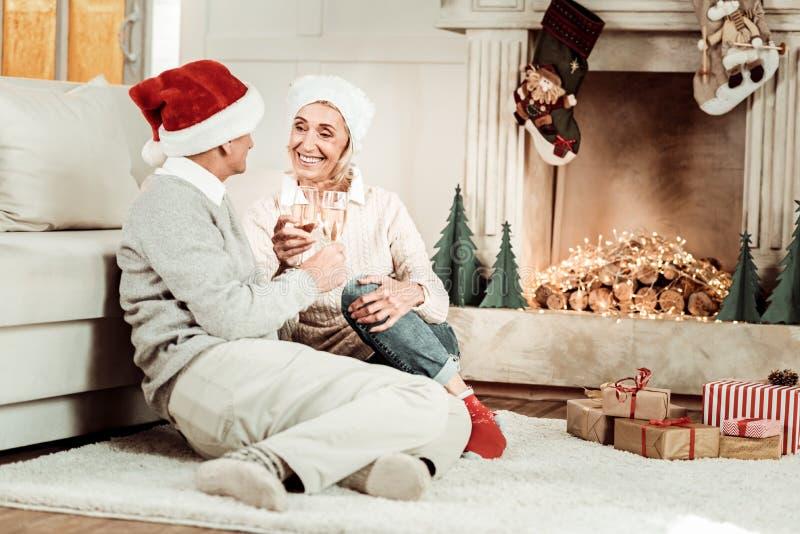 Erfüllte ältere Paare, die Gläser sitzen und halten stockbild