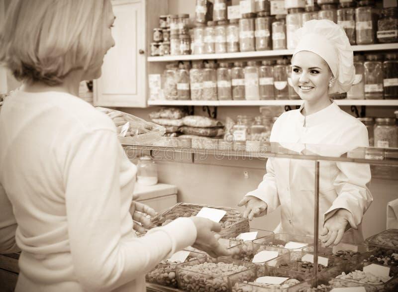 Erfüllte Frau, die verschiedene Nüsse im lokalen Supermarkt kauft stockfoto