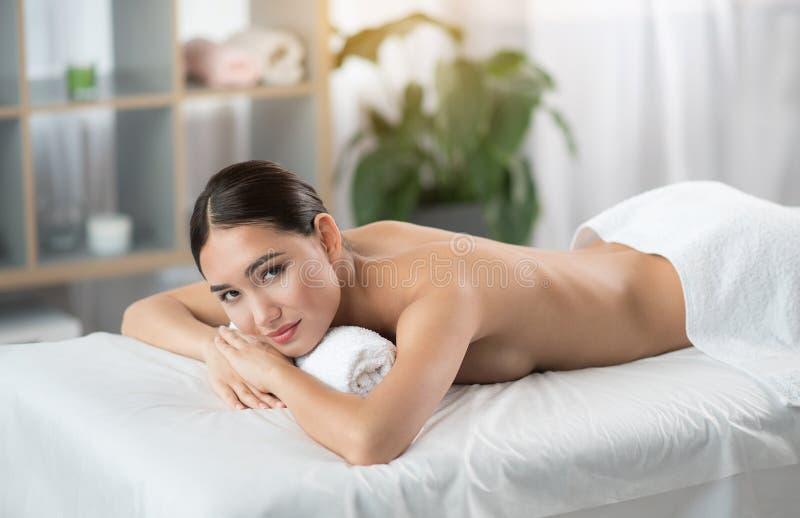 Erfüllte junge Frau, die auf Massagetabelle liegt stockfoto