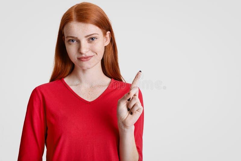 Erfüllte redhaired sommersprossige junge Frau in der roten Kleidung, Punkte mit dem Vorderfinger an der oberen rechten Ecke, zeig lizenzfreie stockfotos