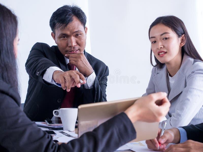 Erfüllter älterer Geschäftsmann, der wachsendes Diagramm an seinen glücklichen Kollegen im Büro zeigt stockfotos