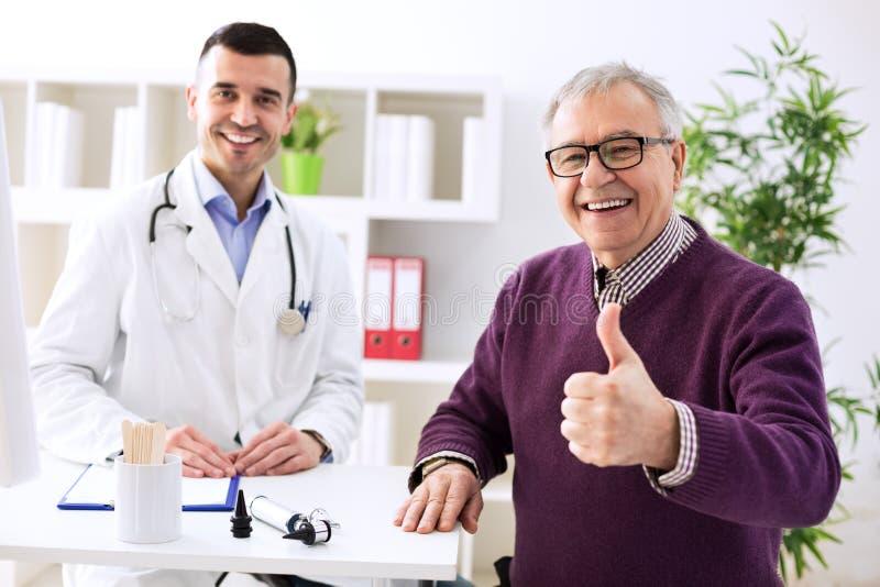 Erfüllter alter Patient mit Erfolgsjungedoktor stockbild