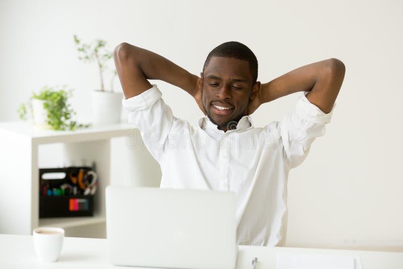 Erfüllter glücklicher Afroamerikanermann, der mit Kaffee und La sich entspannt lizenzfreies stockbild