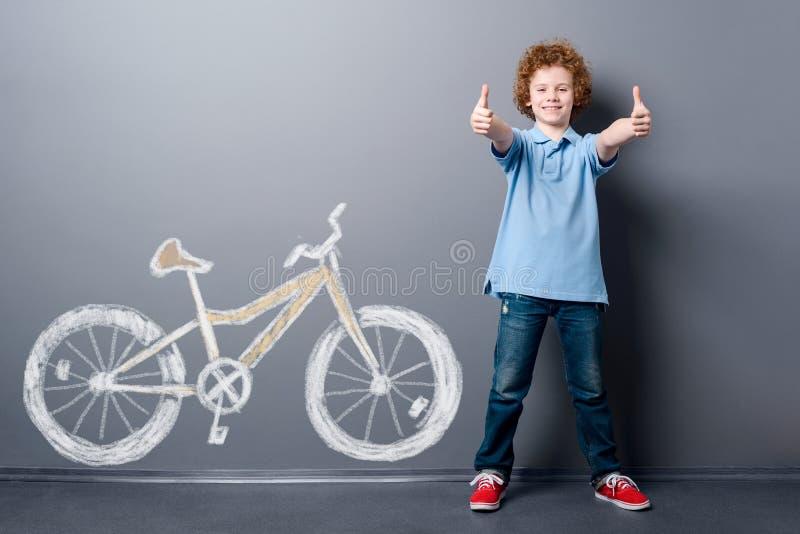 Erfüllter Junge und gelbes Fahrrad lizenzfreies stockfoto