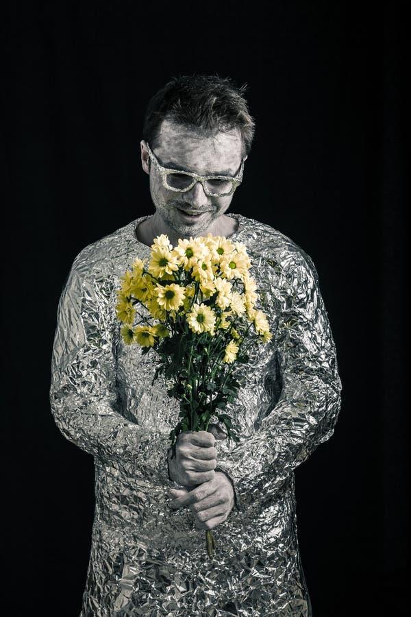 Erfüllter Raumfahrer mit Blumen stockfotos