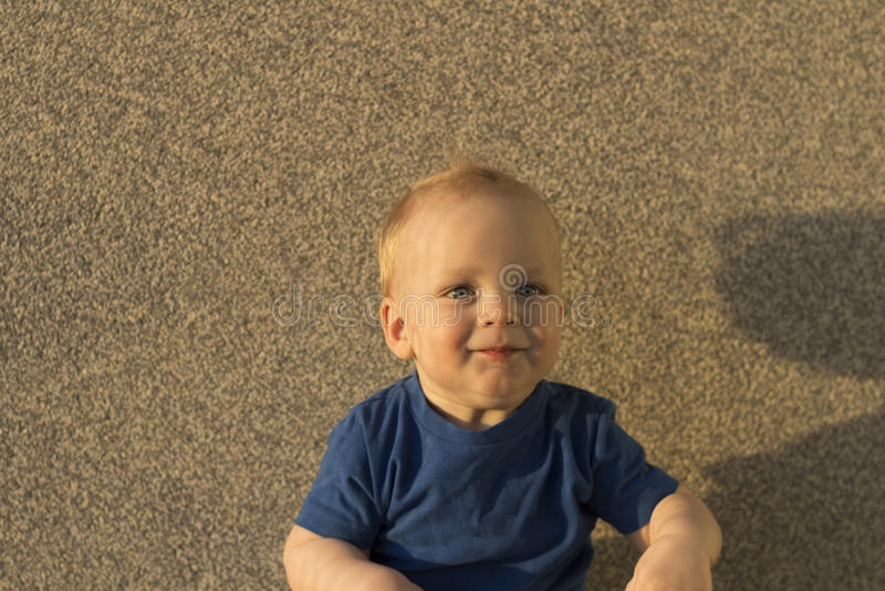 Erfülltes Baby vor dem hintergrund einer Betonmauer Säuglingskind mit ungewöhnlichen Schatten auf seinem Gesicht stockfotos