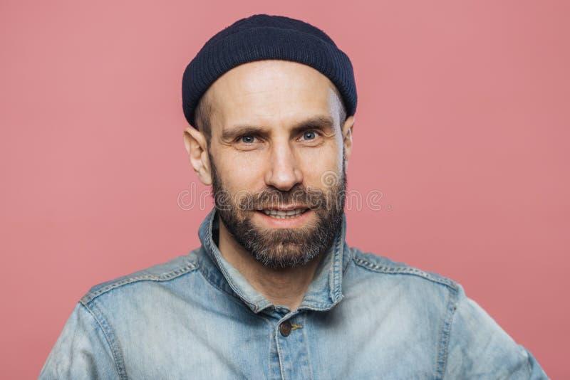 Erfülltes männliches Modell mit starken Bart und dem Schnurrbart untersucht mit überzeugtem Ausdruck Kamera, trägt modernen Hut u lizenzfreies stockfoto