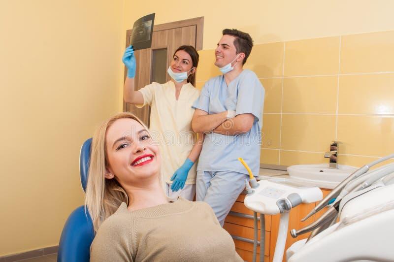 Erfülltes zahnmedizinisches Team und weiblicher Patient stockfoto