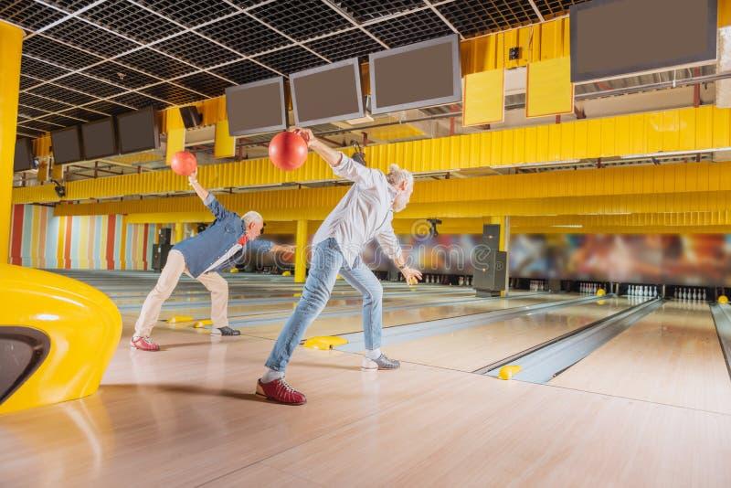 Erfahrene ältere Bowlingspielspieler, welche die Bälle werfen lizenzfreie stockfotos