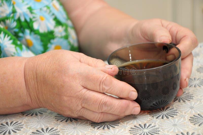 Erfahrene Arbeiter, die Glas mit Tee halten stockfotos