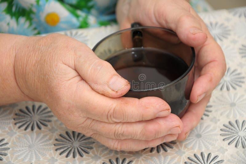 Erfahrene Arbeiter, die mit Kappe des Tees sich wärmen lizenzfreie stockfotos
